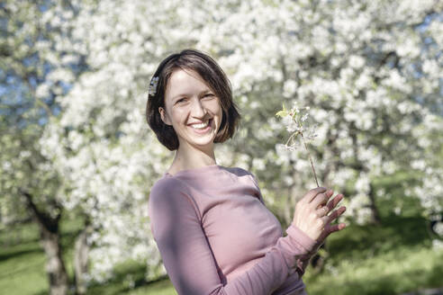 Portrait of happy woman with twig of blossoming cherry tree in garden - EYAF00894