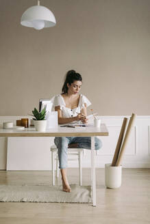 Young woman sitting at table at home - JPF00411