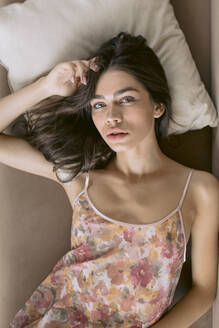 Portrait of beautiful young woman lying in bed - JPF00417