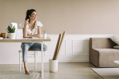 Young woman sitting at table at home - JPF00420