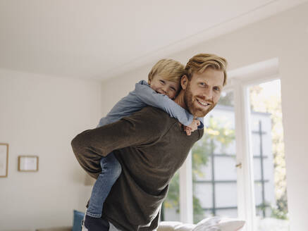 Portrait of happy father carrying son piggyback at home - KNSF07015
