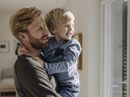 Happy father carrying son at home - KNSF07018