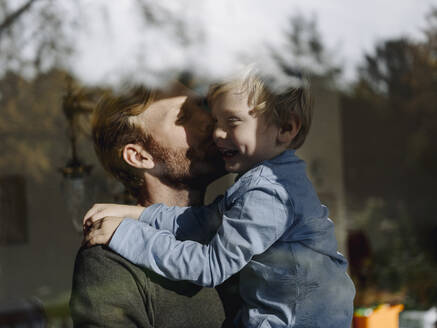 Father carrying and kissing son at the window at home - KNSF07021