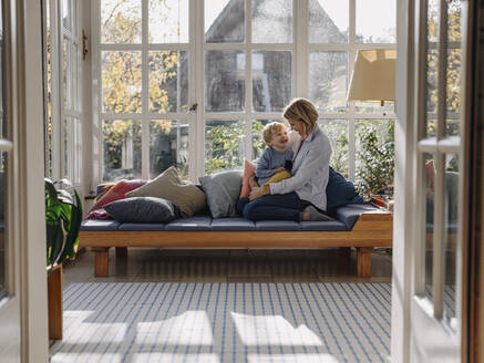 Happy mother and son in sunroom at home - KNSF07027