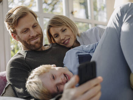 Happy family using cell phone in sunroom at home - KNSF07030