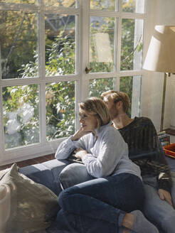 Relaxed couple looking out of window in sunroom at home - KNSF07033