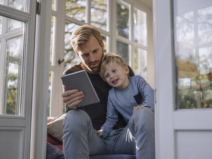 Father and son using tablet in sunroom at home - KNSF07039