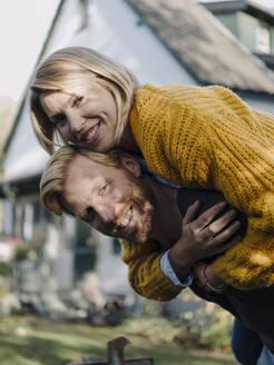 Portait of happy man giving his wife a piggyback ride in garden - KNSF07051