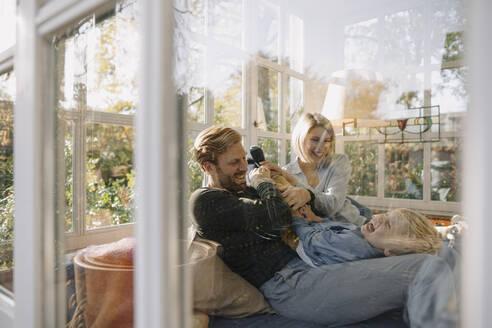 Happy family having fun in sunroom at home - KNSF07078