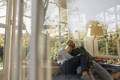 Affectionate couple relaxing in sunroom at home - KNSF07081