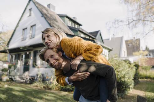 Man giving his wife a piggyback ride in garden - KNSF07096