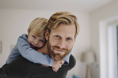 Portrait of smiling father carrying son piggyback at home - KNSF07114