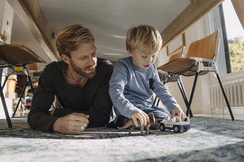 Father and son playing with dinosaur figure and toy car under the table at home - KNSF07120