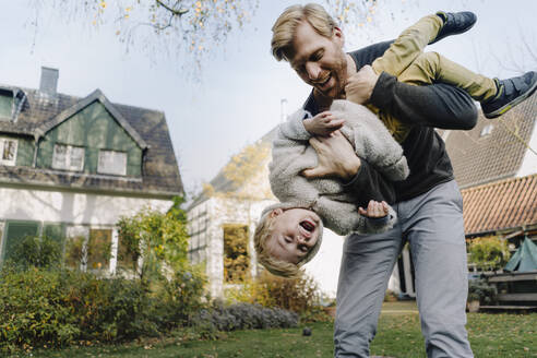 Happy father playing with son in garden - KNSF07138
