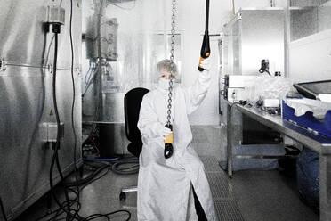 Boy in workwear in a laboratory - KMKF01216