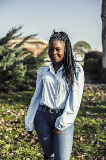 Portrait of smiling young woman with black braids - ACPF00671