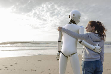 Smiling woman standing arm in arm with robot on the beach - KSHSF00025