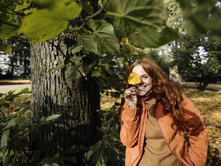 Portrait of happy redheaded woman holding autumn leaf - KNSF07153