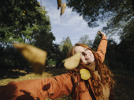 Happy redheaded woman enjoying autumn in a park - KNSF07159