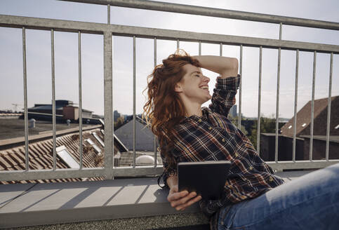 Happy redheaded woman with tablet relaxing on rooftop terrace - KNSF07162