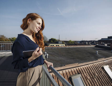 Smiling redheaded woman with tablet on rooftop terrace - KNSF07168