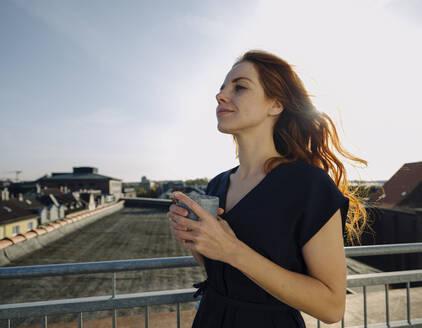 Smiling redheaded woman having a coffee break on rooftop terrace - KNSF07171
