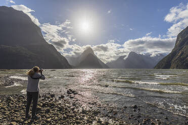 New Zealand, Female tourist photographing scenic landscape of Milford Sound - FOF11614