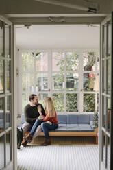 Happy couple sitting in winter garden, talking, holding hands - KNSF07214