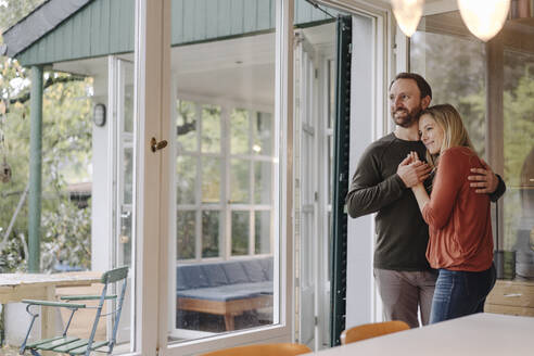 Happy couple embracing in their comfortable home - KNSF07217