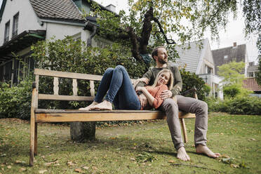 Couple relaxing on bench, enjoying nature in their garden - KNSF07223