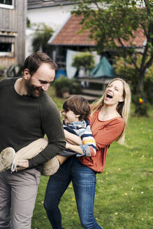 Parents and son having fun, playing in the garden - KNSF07238