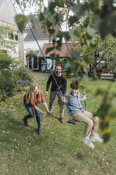 Son swinging in garden with parents pushing him - KNSF07247