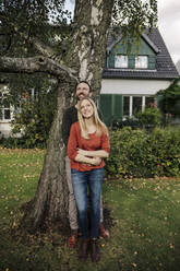 Affectionate couple standing in garden of their new home, looking up - KNSF07250