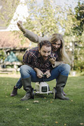 Laughing couple pretending to ride a toy car in the garden - KNSF07259