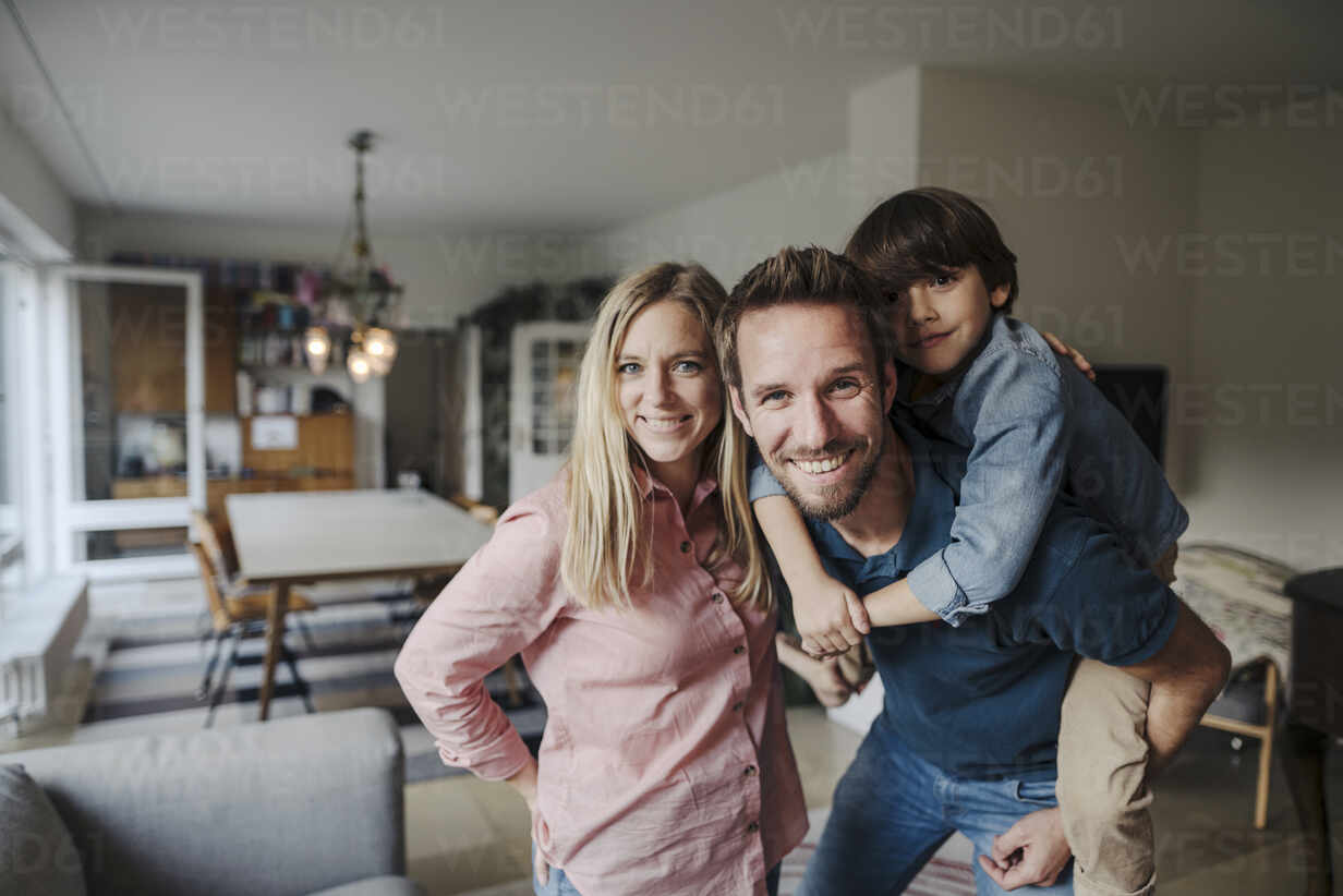 Happy family standing in livingroom, smiling at camera - KNSF07271 - Kniel Synnatzschke/Westend61