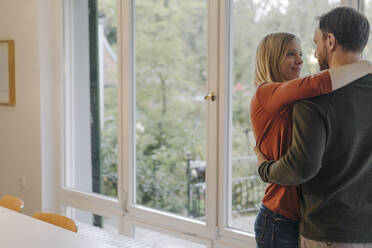 Happy couple embracing in their comfortable home - KNSF07307