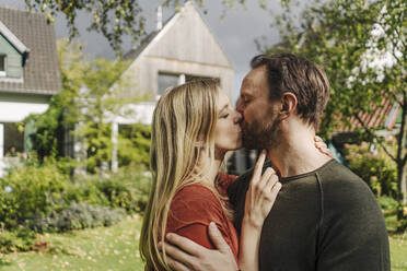 Happy couple kissing in garden, in front of their dream house - KNSF07313