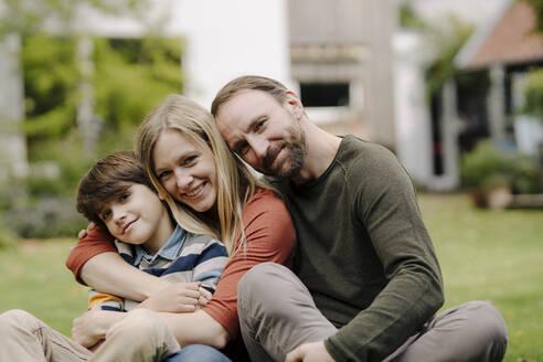 Happy family sitting on grass in their garden - KNSF07319