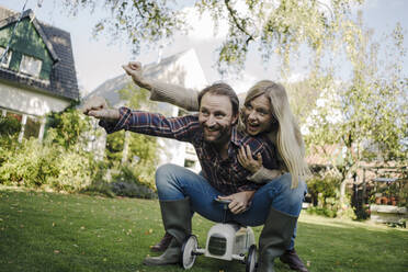 Laughing couple, pretending to fly on a toy car in the garden - KNSF07331