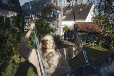 Blond woman swinging in her garden - KNSF07337