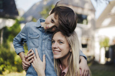 Mother embracing son in the garden of their home - KNSF07346