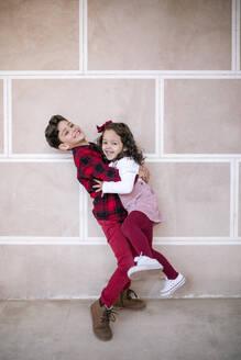 Boy lifting up girl at a wall - GRCF00106