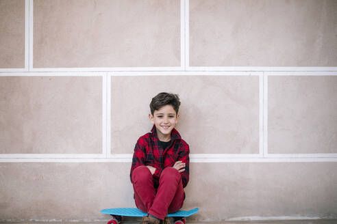 Portrait of smiling boy sitting on skateboard at a wall - GRCF00112