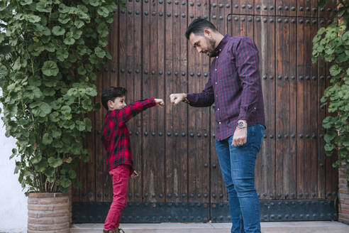 Father and son fist bumping outdoors - GRCF00121