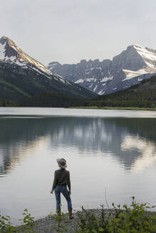 Rear view of female hiker looking at view while standing on shore by Swiftcurrent Lake - CAVF73558