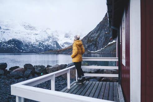 Tourist enjoying the view at Hamnoy, Lofoten, Norway - DGOF00072