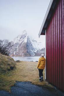Tourist enjoying the view at Hamnoy, Lofoten, Norway - DGOF00105