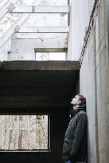 Man leaning at concrete wall of a ruin looking up - EYAF00904