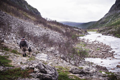 Fly fishermen hiking along river bank with mountains, Lakselv, Norway - DHEF00072