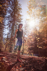 Woman jogging in autumn forest, stretching for warm up - DHEF00091